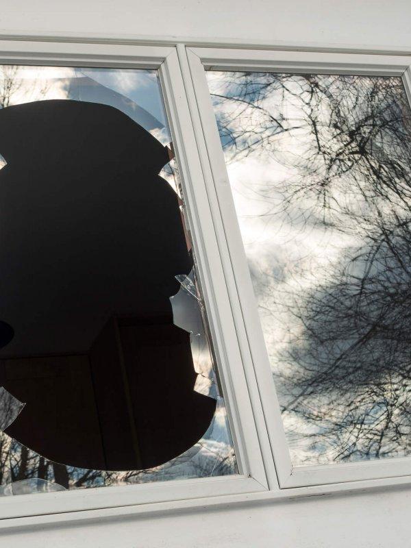 vandalized broken window on house
